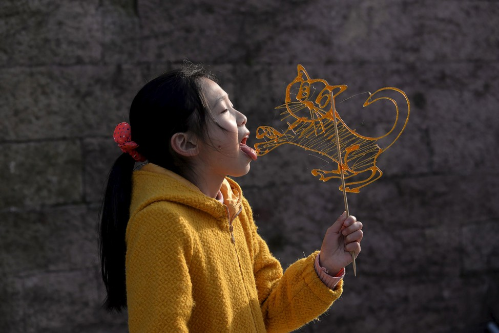A girl licks a traditional candy in the shape of a tiger at a folk art exhibition in Ningbo