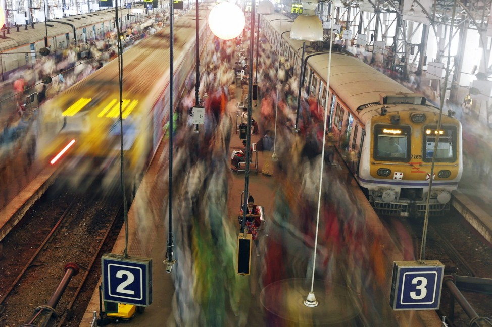 Commuters disembark from crowded suburban trains during the morning rush hour at Churchgate railway station in Mumbai