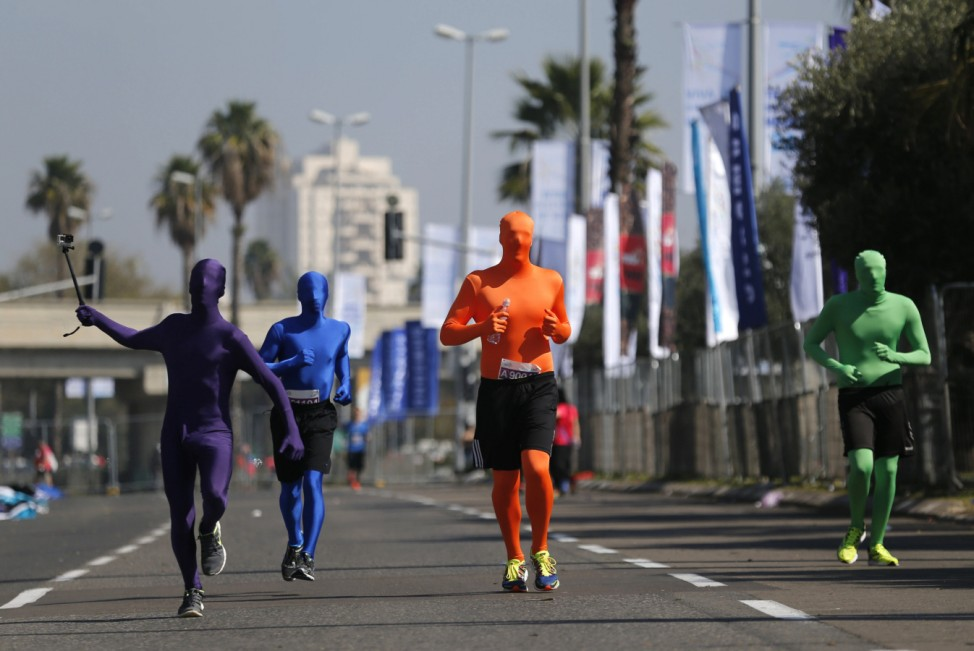 Runners wearing full solid-coloured bodysuits take part in a marathon in Tel Aviv