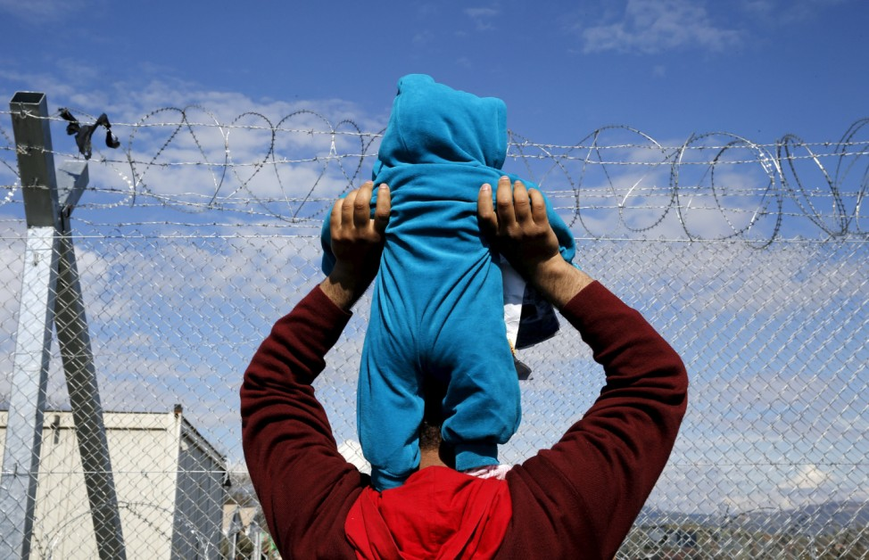 A stranded refugee lifts his child in front of a fence as he and hundreds of others take part in a protest at the Greek-Macedonian border near the Greek village of Idomeni