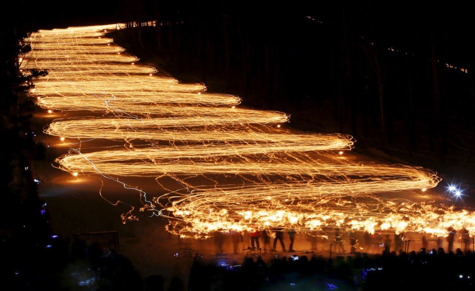 Spectators watch hundreds of skiers descend from a slope while holding lit torches in the town of Zheleznogorsk