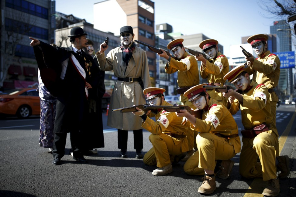 Performers acting as Japanese soldiers pose on a street as they take part in a re-enactment of the Independence Movement Day in Seoul