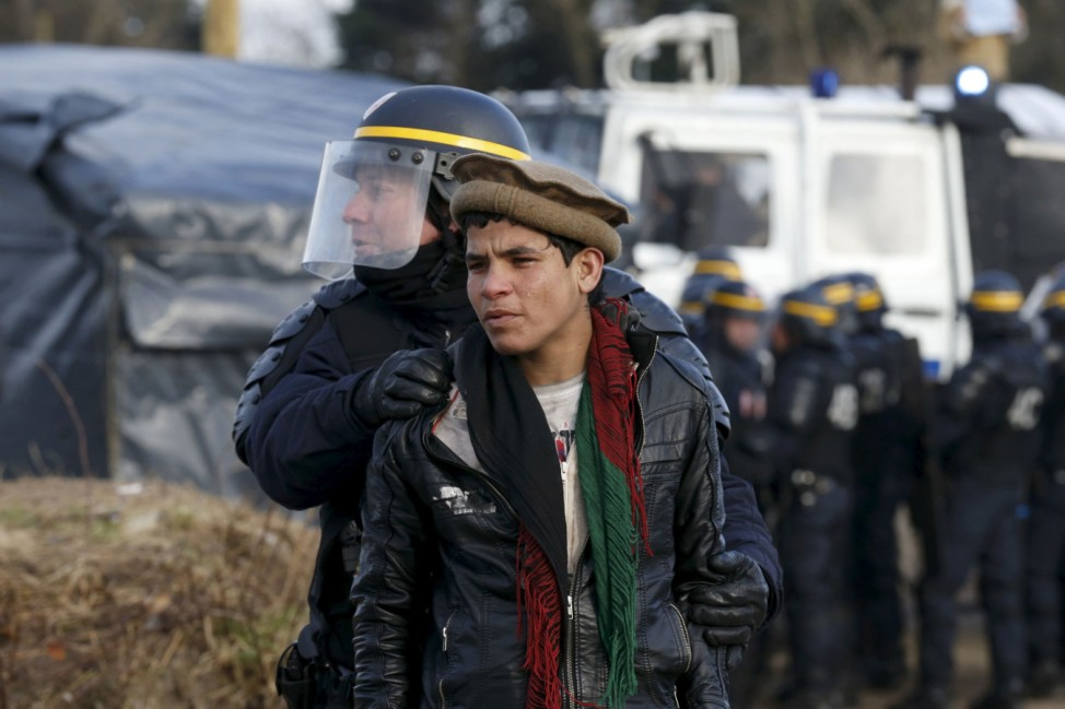 A French CRS riot policeman apprehends a young Afghan during a protest by migrants against the partial dismantlement of the camp for migrants called the 'jungle', in Calais