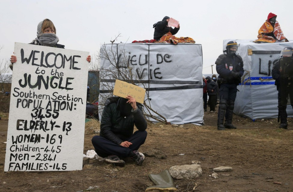 French riot police secure the area as activists and migrants sits on their makeshift shelters during the partial dismantlement of the camp for migrants called the 'jungle', in Calais