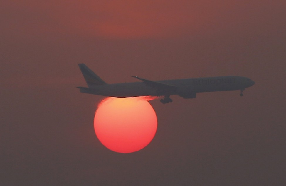 A plane flies over the setting sun in the sky at Beijing International Airport