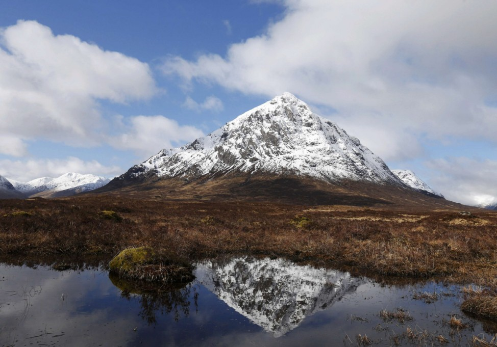 The mountain Buachaille Etive Mor is reflected in water near Ballachulish, Scotland