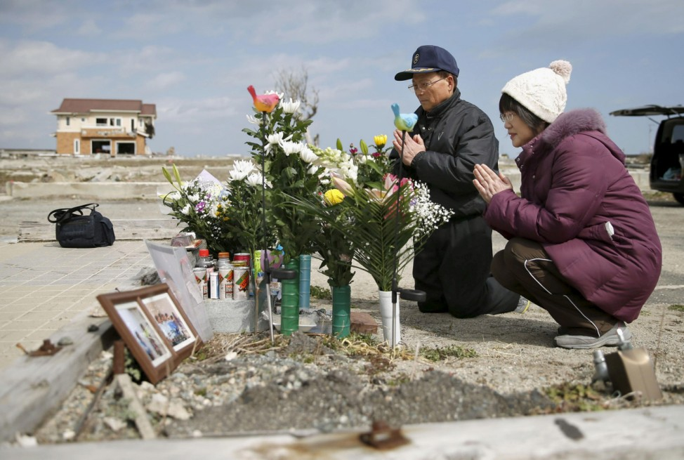 Tsutoshi Yoshida and his wife Seiko pray for their daughter Miki who was killed by the March 11, 2011 earthquake and tsunami in Namie town, Fukushima prefecture, Japan, on the fifth anniversary of the disaster