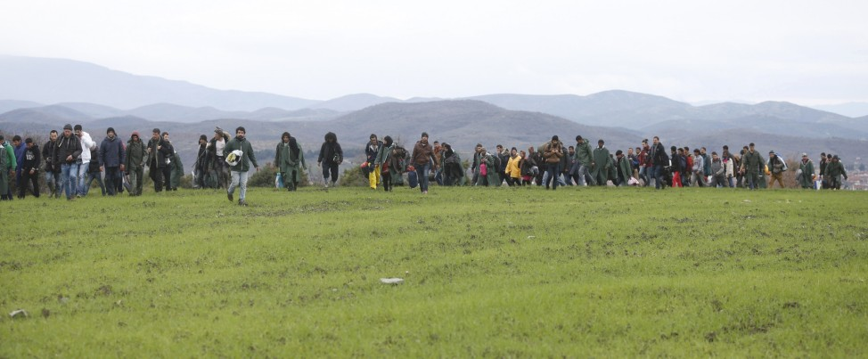 Migrants walk through a field looking for a way to cross the Greek-Macedonian border near the village of Idomeni