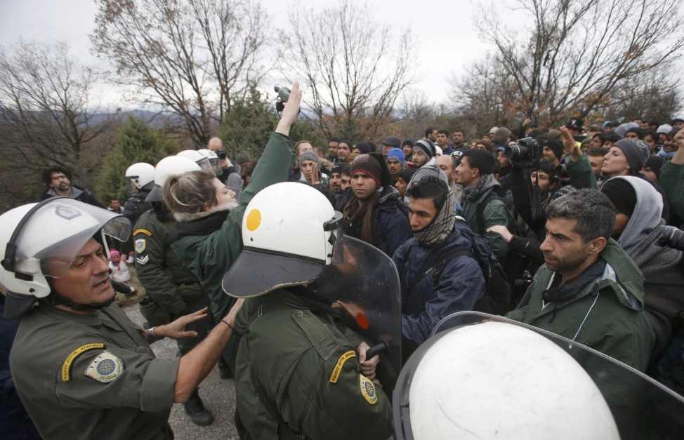 Migrants are stopped by Greek riot police as they look for a way to cross the Greek-Macedonian border near Idomeni