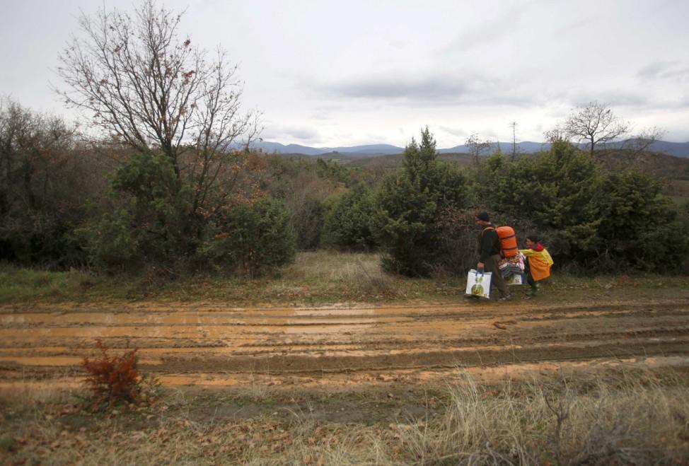 Migrants walk along muddy track looking for a way to cross the Greek-Macedonian border near the village of Idomeni