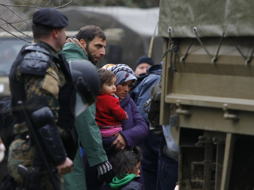 Macedonian soldiers escort migrants who have crossed the border illegally from Greece into army trucks in the village of Moini