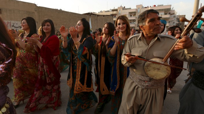 Kurdish women wearing traditional clothes dance during a celebration for Kurdish outfit day in the northeast Syrian Kurdish city of Qamishli