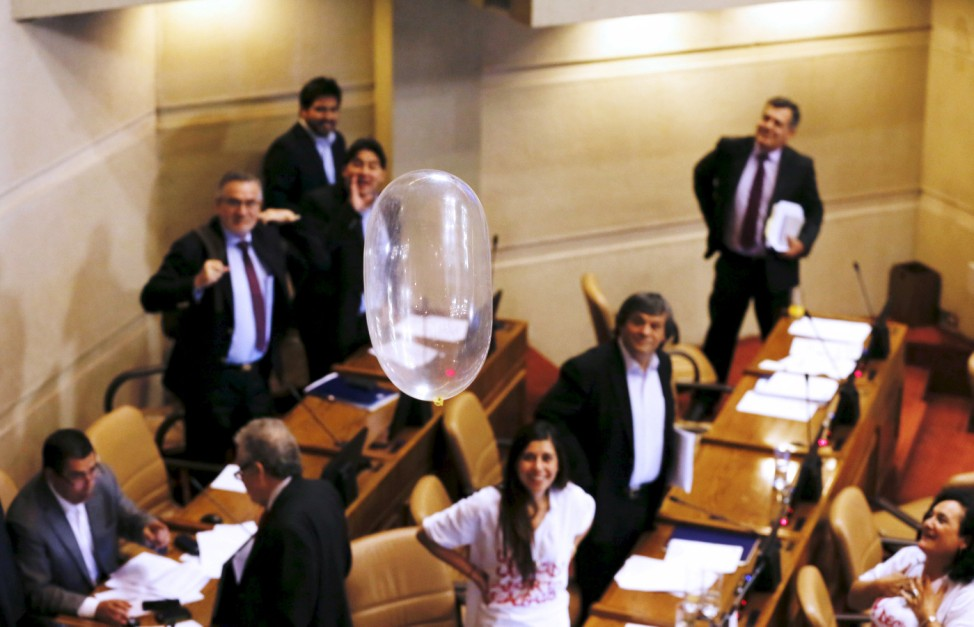 Deputies of Socialist Party, observe a condom floating thrown from the stands, during a session at the congress in favor of a draft law by the government, which seeks to ease the country's strict abortion ban, in Valparaiso, Chile