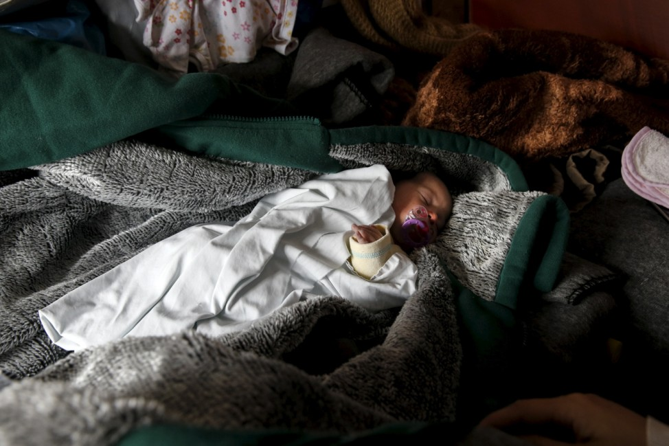 File photo shows ten-day-old newborn baby Zaynab sleeps next to her mother Shukria Al Bakr, 19, from Idlib, Syria, inside a tent at a makeshift camp for refugees and migrants at the Greek-Macedonian border, near the village of Idomeni