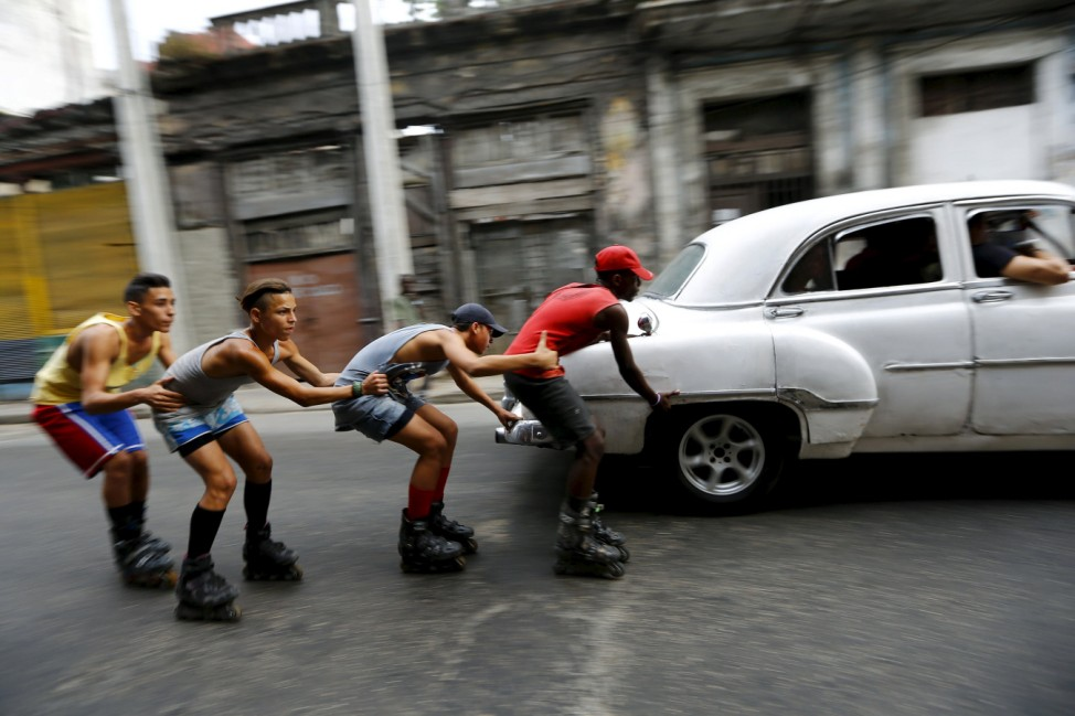 Teenagers on roller skates hold on to each other as they are pulled by a vintage car to move along a street in Havana
