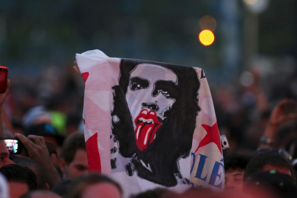 Fans hold an image of late revolutionary hero Ernesto 'Che' Guevara with the symbol of the British band Rolling Stones before their free outdoor concert at Ciudad Deportiva de la Habana sports complex in Havana