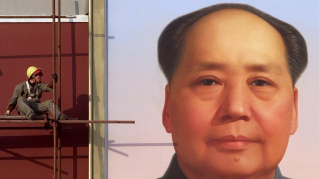 A CHINESE WORKER LOOKS AT A PORTRAIT OF THE LATE CHAIRMAN MAO ZEDONG IN BEIJING