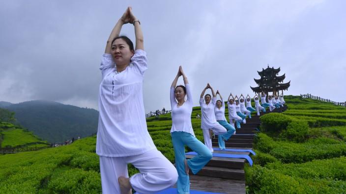 People perform yoga at a tea culture park in Enshi