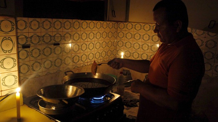 A man cooks lighted by candles lights at his home during a power cut in San Cristobal