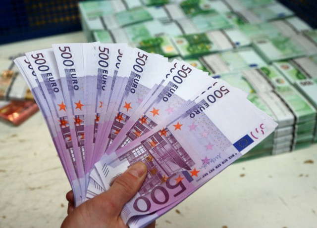 An employee holds 500 euro banknotes in the Money Service Austria company's headquarters in Vienna