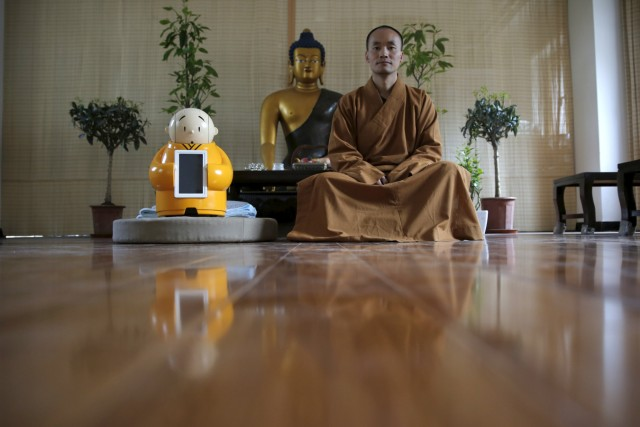 Master Xianfan sits next to robot Xian'er as he poses for photograph at Longquan Buddhist temple on the outskirts of Beijing