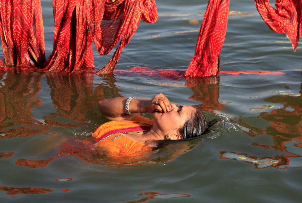 A Hindu devotee takes a holy dip in the Shipra river at the Simhastha Kumbh Mela in Ujjain