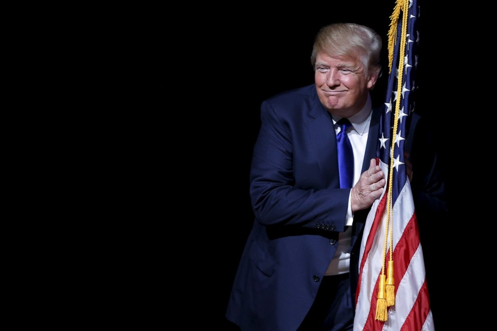 U.S. Republican presidential candidate Trump hugs a U.S. flag as he takes the stage for a campaign town hall meeting in Derry