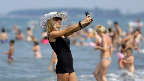 People enjoy a hot day on the beach of the Black Sea in Ureki