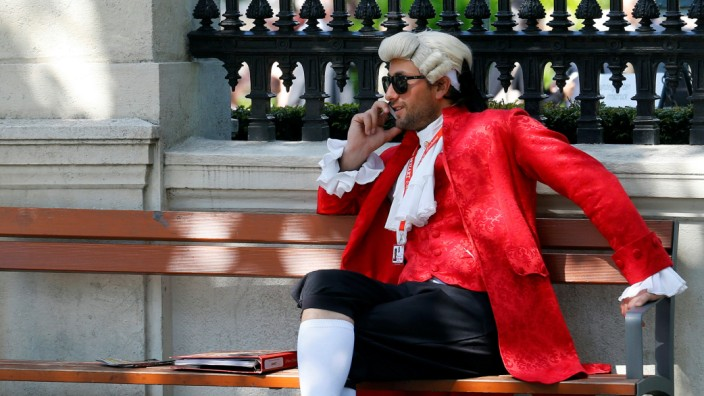 A concert ticket vendor dressed in a historic costume sits on a bench while making a phone call in Vienna, Austria