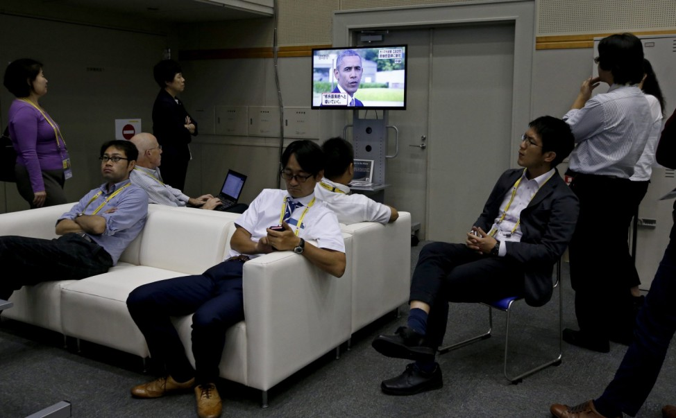 Japanese journalists watch a breaking news