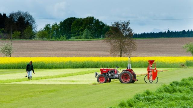 Landwirtschaft: Ein kleiner roter Traktor hilft beim Ausbringen neuen Saatguts.