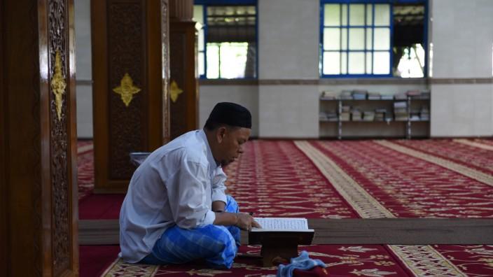 Außenansicht: Ein Muslim liest im Koran.