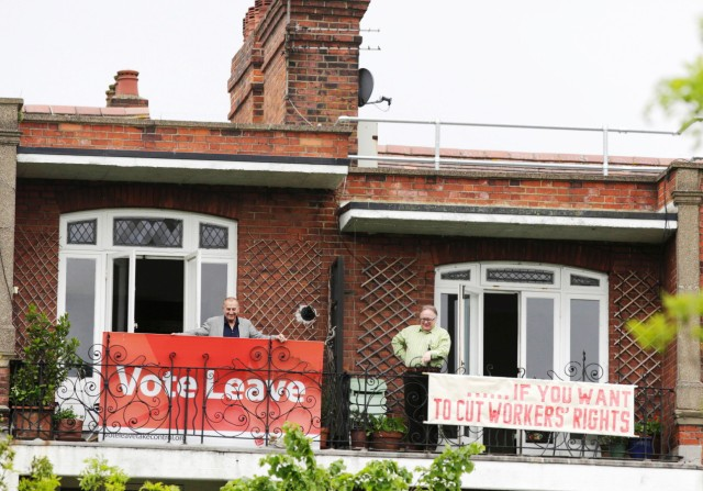 Neighbours Tony (L) and Frank pose for cameras after hanging rival EU referendum banners from their balconies in north London