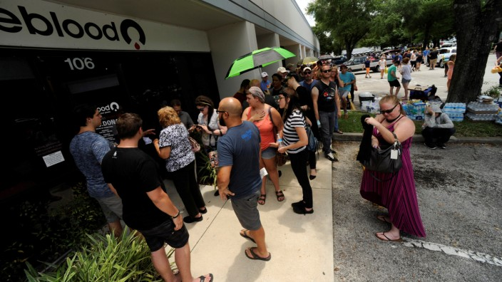 Hundreds of community members line up outside a clinic to donate blood after an early morning shooting attack at a gay nightclub in Orlando