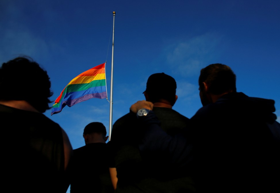 Mourners gather under an LGBT pride flag flying at half-mast for a candlelight vigil in remembrance for mass shooting victims in Orlando, from San Diego, California