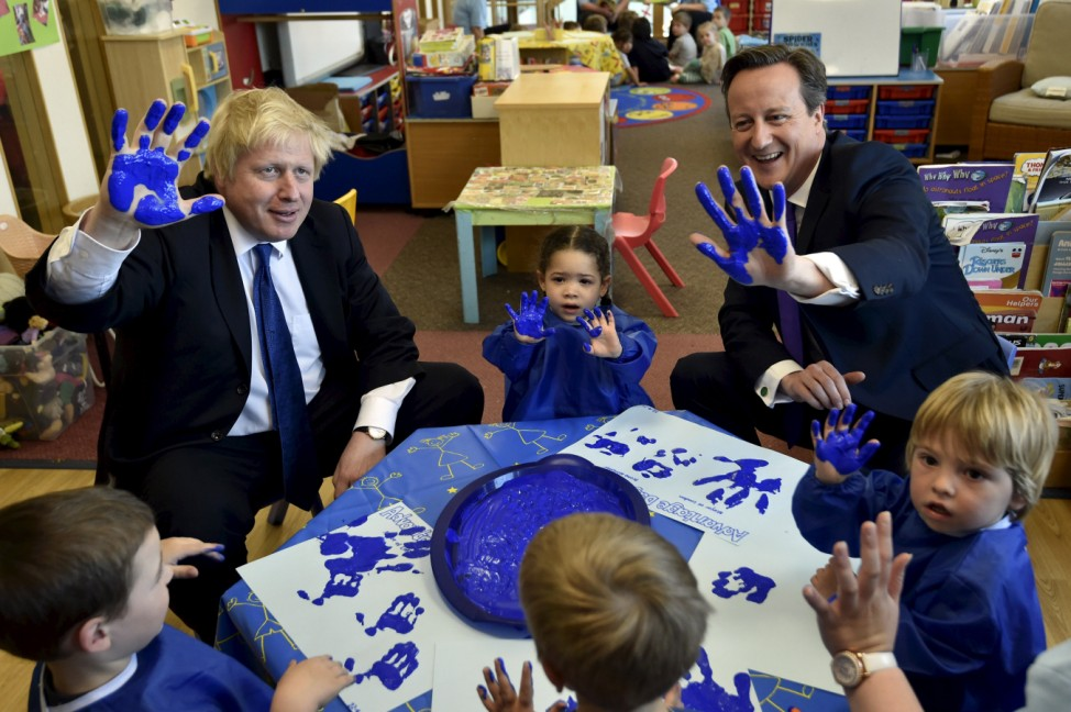 Britain's Prime Minister Cameron and London Mayor Johnsonreact as they join a hand-printing session with children at the Advantage children's daycare nursery in Surbiton in south west London