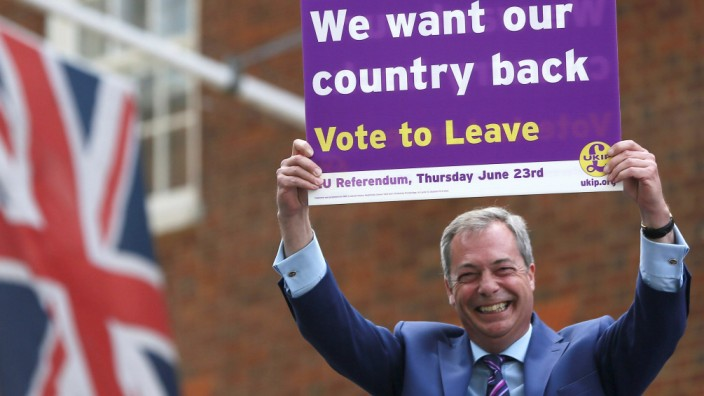 Leader of the United Kingdom Independence Party Nigel Farage holds a placard as he launches his party's EU referendum tour bus in London