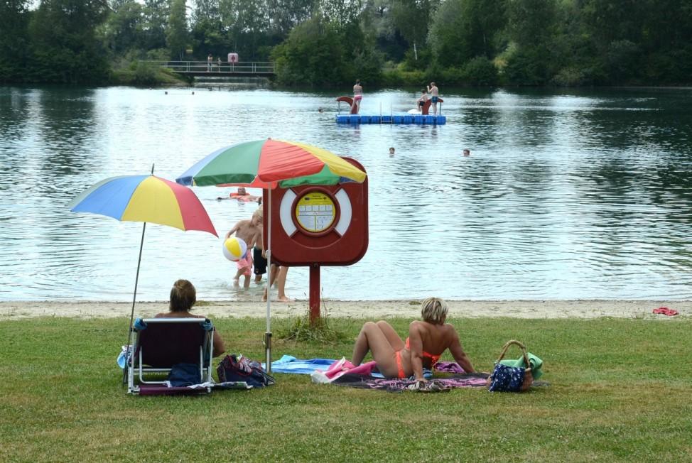 Menschen baden am Moosinninger Weiher, einem See im Landkreis Erding.