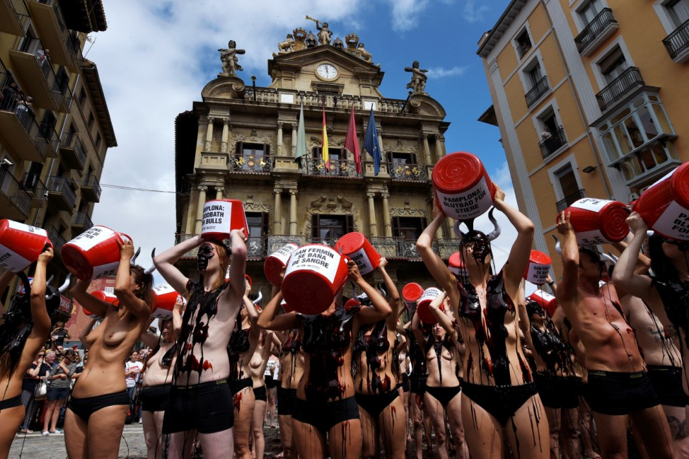 Animal rights protesters throw fake blood onto themselves as they protest for the abolition of bull runs and bullfights a day before the start of the famous running of the bulls San Fermin festival in Pamplona