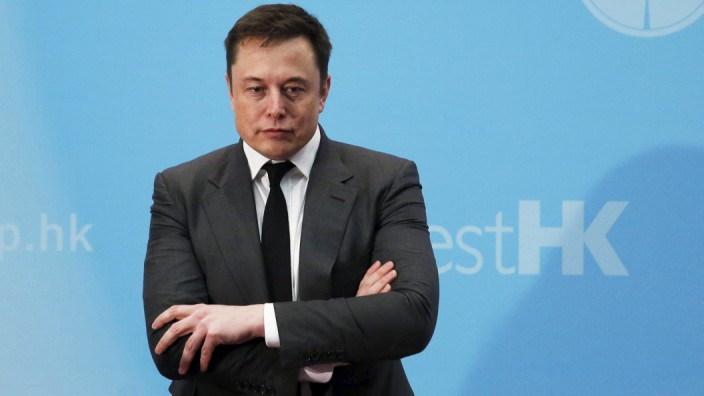 Tesla Chief Executive Elon Musk stands on the podium as he attends a forum on startups in Hong Kong