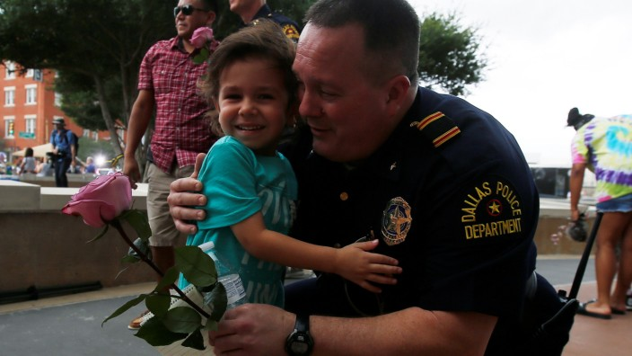 A child hugs a Dallas police officer at Dallas Police Headquarters following the multiple police shootings in Dallas