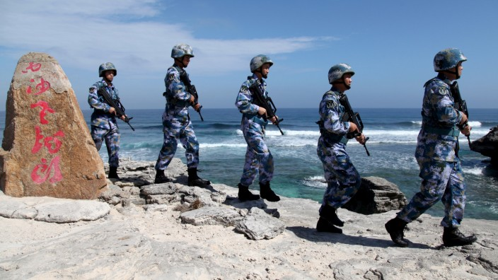 Soldiers of China's People's Liberation Army Navy patrol at Woody Island, in the Paracel Archipelago, which is known in China as the Xisha Islands