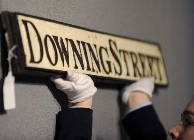 Furniture specialist Burt poses for photographers with an old street sign for Downing Street, at Bonhams auctioneers in central London