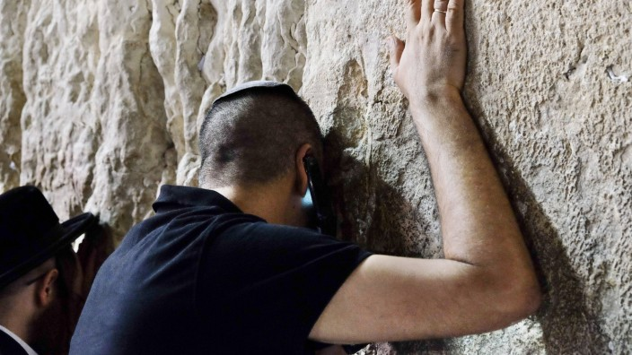 Sept 30 2014 Jerusalem Israel A man leans on the Kotel verbally reciting Amen repeatedly to i