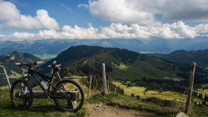 EIn Mountainbike steht an einer Holzbank auf dem Gipfel des Riedberger Horns .Balderschwang, Bayern,