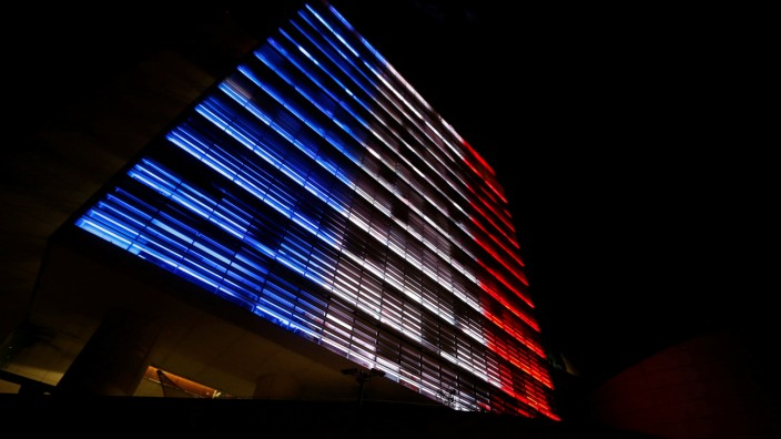 The Senate building is lit up in blue, white and red, the colors of the French flag in Mexico City