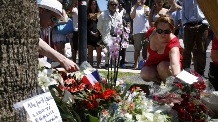 A woman places a bouquet of flowers as people pay tribute near the scene where a truck ran into a crowd at high speed killing scores and injuring more who were celebrating the Bastille Day national holiday in Nice