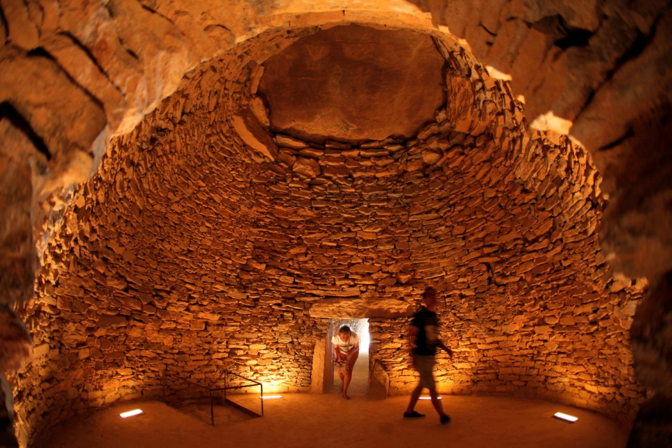 People walk inside the Tholos de El Romeral dolmen at Antequera Dolmens Site in Antequera