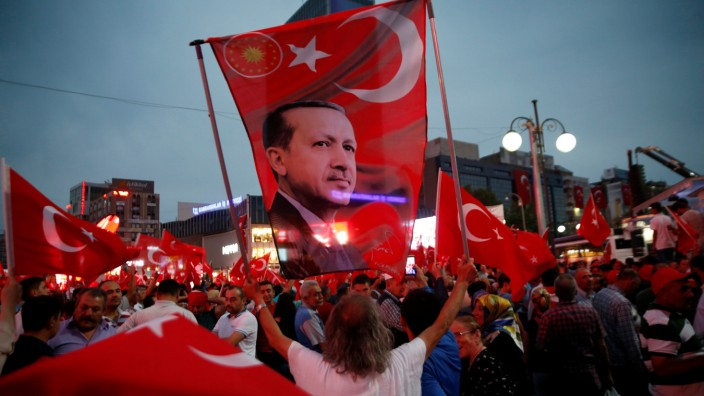 A supporter holds a flag depicting Turkish President Tayyip Erdogan during a pro-government demonstration in Ankara, Turkey