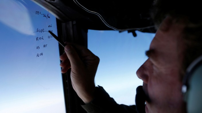 Squadron leader Brett McKenzie marks the name of another search aircraft on the windshield of a Royal New Zealand Air Force P-3K2 Orion aircraft searching for missing Malaysian Airlines flight MH370 over the southern Indian Ocean